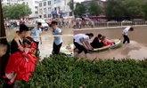 ไม่หวั่นแม้พายุมา โซเชียลจีนแชร์สนั่น บ่าวสาวลุยน้ำท่วมเข้าพิธีวิวาห์